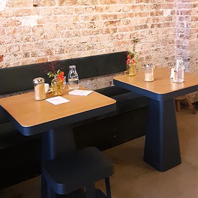 Les tables en bois et le mur en brique de Mignon Café